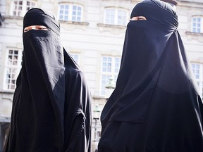 Women in niqab walk in front of the Danish Parliament at Christiansborg Castle, in Copenhagen, Denmark, Thursday May 31. 2018. (AP)