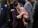 NDP Member of Parliament Christine Moore carries her daughter Daphnee after casting her ballot for a new Speaker in the House of Commons on Parliament Hill in Ottawa, Dec. 3, 2015.