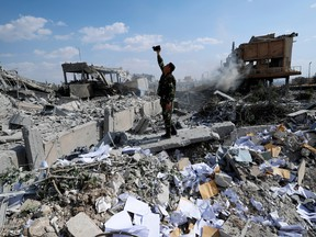 A Syrian soldier films the damage of the Syrian Scientific Research Center which was attacked by U.S., British and French military strikes to punish President Bashar Assad for suspected chemical attack against civilians, in Barzeh, near Damascus, Syria on Saturday, April 14, 2018. (AP Photo/Hassan Ammar)