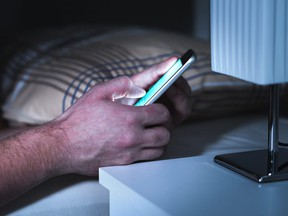 In this stock photo, a man texts on a phone in a dark bedroom.