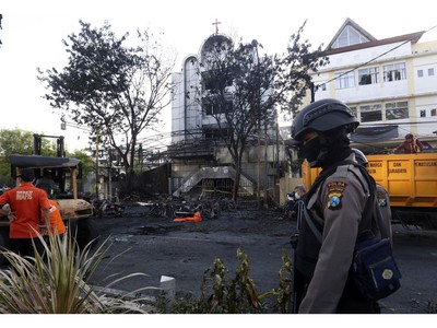 A police officer stands guard at one of the sites of church attacks in Surabaya, East Java, Indonesia, Sunday, May 13, 2018.