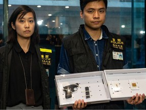 Police officers display a seized handgun and ammunition as evidence after a woman shot and wounded four people at a park in Taikoo Shing in Hong Kong on June 26, 2018.  At least four people were injured in a shooting at a park in Hong Kong on June 26, police said, a rare attack in the southern Chinese city which has a reputation for safety.