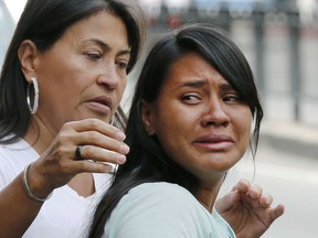 Barbara Barca, right, a survivor of the stampede at a crowded nightclub, cries as she leaves police headquarters in Caracas, Venezuela, Saturday, June 16, 2018. Venezuela's government says 17 people were killed early Saturday after a tear gas device was set off during a nightclub brawl in the capital, leading hundreds of people to flee.