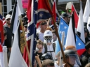 In this Saturday, Aug. 12, 2017, photo white nationalist demonstrators walk into the entrance of Lee Park surrounded by counter demonstrators in Charlottesville, Va.