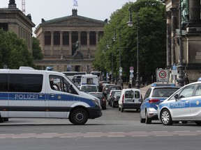 Police vehicles stand in front of Berlin Cathedral, Sunday June 3, 2018. Berlin police say an officer has opened fire near the German capital's cathedral, slighting injuring a man.