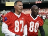 In this July 12, 2014, file photo, former San Francisco 49ers wide receivers Dwight Clark, left, and Jerry Rice, right, walk together on the field in San Francisco.