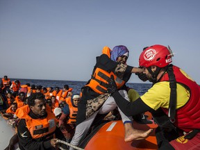 """A migrant aboard a rubber dinghy off the Libyan coast is helped by rescuers aboard the Open Arms aid boat, of Proactiva Open Arms Spanish NGO, Saturday, June 30, 2018. 60 migrants were rescued as Italy's right-wing Interior Minister Matteo Salvini tweeted: """"They can forget about arriving in an Italian port."""""""