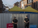 Police secure a point of interest in Salisbury, where counter-terrorism officers are investigating after a woman and her partner were exposed to the nerve agent Novichok, Monday July 9, 2018. (AP Photo/Steve Parsons)