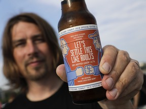 Samuli Huuhtanen, CEO of Finnish beer brewery Rock Paper Scissors displays a beer bottle labeled with cartoon caricatures depicting Russian President Vladimir Putin and U.S President Donald Trump, during an interview with the Associated Press in Helsinki, Saturday, July 14, 2018. (AP Photo/Markus Schreiber)