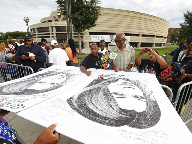 People in line sign well wishes on poster boards outside the Charles H. Wright Museum of African American History during a public visitation for Aretha Franklin in Detroit, Wednesday, Aug. 29, 2018. Franklin died Aug. 16, of pancreatic cancer at the age of 76. (AP Photo/Paul Sancya)