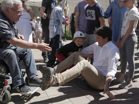 Duncan Mayor Phil Kent reaches out to grab Prime Minister Justin Trudeau's hand after his slips while trying to stand up after talking to Kent at the Duncan Farmers Market in Duncan, B.C., on Saturday, Aug. 4, 2018.