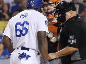 Los Angeles Dodgers' Yasiel Puig, left, and San Francisco Giants catcher Nick Hundley, center, argue while home plate umpire Eric Cooper gets between them during the seventh inning, Tuesday, Aug. 14, 2018, in Los Angeles.