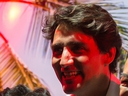 Prime Minister Justin Trudeau is illuminated by a red spotlight as he poses for a photograph with Richmond Night Market staff during a visit to the market in Richmond, B.C., on Saturday Aug. 4, 2018.