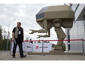A visitor passes a model of a guided robot-style system presented by the Concern Kalashnikov during the International Military Technical Forum Army-2018 in Alabino, outside Moscow, Tuesday, Aug. 21, 2018.