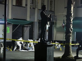 Crime scene workers cover the bodies of victims of a shooting in Garibaldi Plaza, in Mexico City, Friday Sept. 14, 2018.