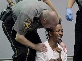 Shyhiem Adams is aided by a court marshal after collapsing as friends of the Justin Brady were screaming at Adams during his arraignment in Enfield Superior Court Tuesday, Sept. 11, 2018, in Enfield, Conn. (Jim Michaud/Journal Inquirer via AP, Pool)