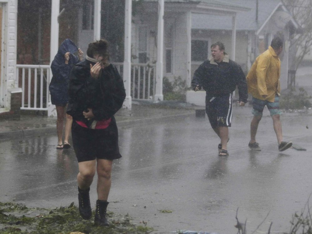 People walk through the high winds from Hurricane Florence in downtown Swansboro N.C., Friday, Sept. 14, 2018. (AP Photo/Tom Copeland)