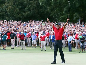 Tiger Woods of the United States celebrates making a par on the 18th green to win the Tour Championship at East Lake Golf Club on Sept. 23, 2018 in Atlanta, Ga.