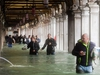 Tourists under arches next to the flooded St Mark's Square during a high-water (Acqua Alta) alert in Venice on October 29, 2018. - The flooding, caused by a convergence of high tides and a strong Sirocco wind, reached around 150 centimetres on October 29, 2018. (Photo by Miguel MEDINA / AFP)MIGUEL MEDINA/AFP/Getty Images
