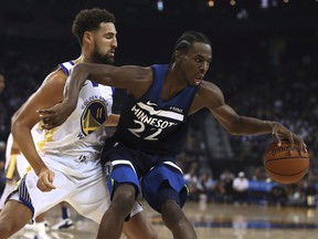 Minnesota Timberwolves' Andrew Wiggins, right, keeps the ball from Golden State Warriors' Klay Thompson (11) during the first half of an NBA preseason basketball game Saturday, Sept. 29, 2018, in Oakland, Calif. (THE CANADIAN PRESS/AP/Ben Margot)