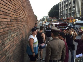 In this Thursday, Oct. 18, 2018, photo, Canadian Brittney Schneider, left, and Briton Furlong Lee, second left, stand in front of Tha Pae Gate in Chiang Mai province, northern Bangkok, Thailand. They face up to 10 years in prison on charges of spraying paint on an ancient wall in northern Thailand, police said.