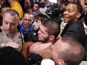 Khabib Nurmagomedov, bottom centre, is held back outside of the cage after fighting Conor McGregor in a lightweight title bout at UFC 229 in Las Vegas, Saturday, Oct. 6, 2018.