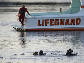 In this Thursday, April 9, 2015 photo, divers emerge from the water as debris believed to be from a car floats to the surface where a car went off the berth and into the water at the San Pedro Slip, across from Ports O'Call in San Pedro, Calif. U.S. prosecutors have charged an Egyptian father with fraudulently collecting insurance payouts after driving his family off a Los Angeles pier and killing his two severely autistic sons. Prosecutors said Tuesday, Nov. 13, 2018, that Ali Elmezayen had purchased $6 million in insurance policies to cover his family in the event of an accidental death two years before the 2015 deaths.