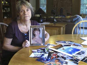 In this Oct. 9, 2018 photo, Linda Marino poses with photographs of her son, Samuel, at her home in Tolland, Conn. Samuel Marino died in a 2009 car crash that relatives believe was intentional after becoming a victim of a male sex trafficking ring. Advocates are calling for more recognition and services for male victims.