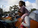 A man carries a girl on his shoulders at a migrant shelter in Tijuana, Mexico, Thursday, Nov. 22, 2018.