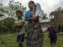 Claudia Maquin, 27, walks with her three children, Abdel Johnatan Domingo Caal Maquin, 9, left, Angela Surely Mariela Caal Maquin, 6 months, middle, and Elvis Radamel Aquiles Caal Maquin, 5, right, as they leave Domingo Caal Chub's house, Claudia's father in law, in Raxruha, Guatemala, Saturday, Dec. 15, 2018. (AP Photo/Oliver de Ros)