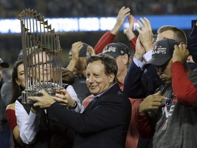 This Oct. 28, 2018, shows Boston Red Sox owner John Henry, partially hidden at left, and chairman Tom Werner holding the championship trophy beside manager Alex Cora, right, after Game 5 of baseball's World Series against the Los Angeles Dodgers in Los Angeles.