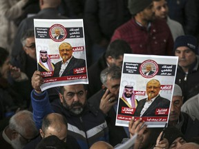 In this Nov. 16, 2018 file photo, members of Arab-Turkish Media Association and friends of Washington Post columnist Jamal Khashoggi hold posters showing images of Saudi Crown Prince Muhammed bin Salman and of Khashoggi, as they attend funeral prayers in absentia for him following his killing the previous month in the Saudi Arabia consulate, in Istanbul.
