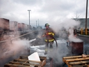 A fireman works to extinguish a burning barrel at Canada Posts' Gateway Postal Facility, after union groups and activists blocked truck traffic to and from the facility in support of Canada Post workers who were recently legislated back to work by the federal government, in Mississauga, Ont., Saturday, Dec. 1, 2018.