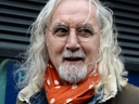 Scottish comedian Billy Connolly stops to speak to the media after leaving floral tributes near The Clutha Bar, on Dec. 3, 2013 in Glasgow, Scotland.