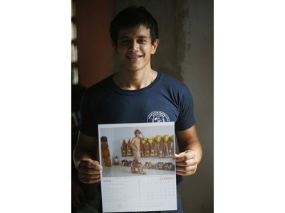 In this Jan. 12, 2019 photo, firefighter Daniel Rodriguez poses holding a calendar page with a nude photo of himself, in Asuncion, Paraguay.
