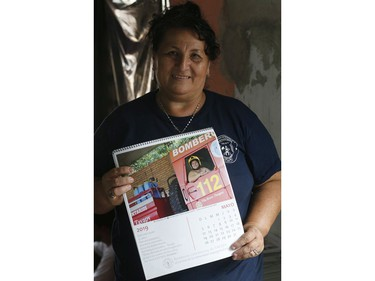 In this Jan. 12, 2019 photo, firefighter Natividad Ayala García holds a calendar page with a photo of herself posing nude inside a fire truck, in Asuncion, Paraguay.