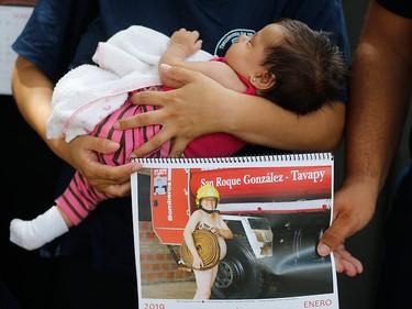 In this Jan. 12, 2019 photo, firefighter Fatima Olmedo holds her two-month-old baby Samara as her husband holds a calendar page with a photo Olmedo posing nude while pregnant, in Asuncion, Paraguay.
