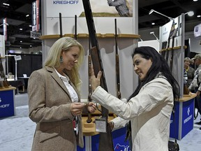 In this Wednesday, Jan. 9, 2019, photo, Rachel Carrie, left, with Krieghoff International, shows Gladys Taggart a Krieghoff K-20 Victoria shotgun designed for women at the SCI Convention at the Reno-Sparks Convention Center in Reno, Nev. (Andy Barron/The Reno Gazette-Journal via AP)