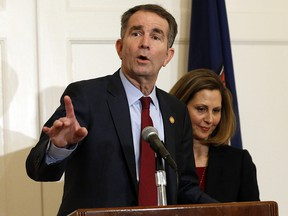 Virginia Gov. Ralph Northam, left, accompanied by his wife, Pam, speaks during a news conference in the Governor's Mansion in Richmond, Va., on Saturday, Feb. 2, 2019. (AP Photo/Steve Helber)