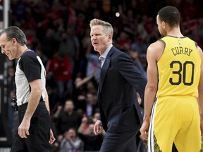 Golden State Warriors coach Steve Kerr, center, yells at referee Ken Mauer, left, after being called for a technical foul, while guard Stephen Curry, right, watches during the second half of an NBA basketball game against the Portland Trail Blazers in Portland, Ore., Wednesday, Feb. 13, 2019.