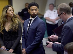 This March 14, 2019 file photo, actor Jussie Smollet, centre, looks at attorney Ron Safer as he stands with his lead attorney Tina Glandian in Cook County Circuit Court in Chicago. (E. Jason Wambsgans/ Chicago Tribune via AP, Pool)