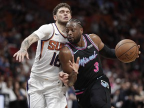Miami Heat guard Dwyane Wade, right, dribbles the ball against Phoenix Suns guard Tyler Johnson during the second half of an NBA basketball game Monday, Feb. 25, 2019, in Miami. (AP Photo/Brynn Anderson)