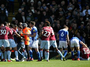 A fan is removed after attacking Aston Villa's Jack Grealish, right, on the pitch during the Sky Bet Championship soccer match at St Andrew's Trillion Trophy Stadium, Birmingham, England, Sunday March 10, 2019.
