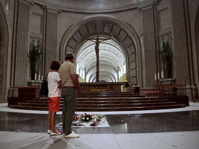 In this file photo taken on Friday, July 13, 2018, people look at the tomb of former Spanish dictator Francisco Franco inside the basilica at the Valley of the Fallen monument near El Escorial outside Madrid. (AP Photo/Andrea Comas, File)
