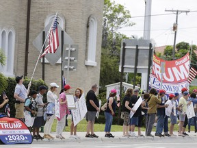 Supporters wait for the Motorcade carrying President Donald Trump returning to Mar-a-Lago on Sunday, March 24, 2019, in West Palm Beach, Fla. (AP Photo/Terry Renna)