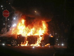 A car burns after petrol bombs were thrown at police in the Creggan area of Derry, in Northern Ireland, Thursday, April 18, 2019.