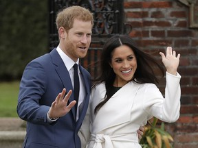 In this Monday, Nov. 27, 2017 file photo, Britain's Prince Harry and his fiancee Meghan Markle pose for photographers during a photocall in the grounds of Kensington Palace in London.