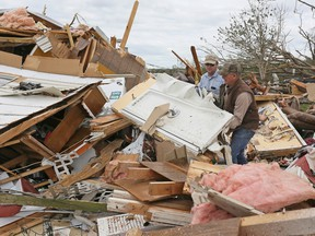 Roman Brown, left and Sam Crawford, right move part of a shower wall out of their way as they help a friend look for their medicine in their destroyed home Sunday, April 14, 2019, along Seely Dr. outside of Hamilton, Miss. after an apparent tornado touched down Saturday, April, 13, 2019.