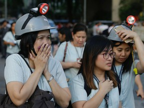 Wearing protective helmets, employees evacuate their office building following an earthquake in Manila, Philippines, on Monday, April 22, 2019.