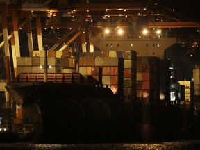 Containers are moved inside the cargo ship M/V Bavaria as it is docked at Subic port in Zambales province, northwestern Philippines on Thursday, May 30, 2019.  (AP Photo/Aaron Favila)